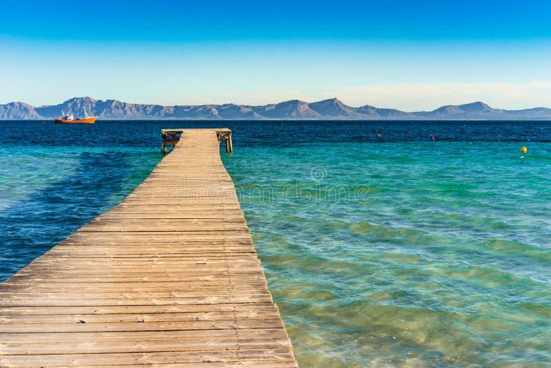 A ilha de Majorca da Espanha, o cais de madeira com mar e a montanha ajardinam na baía da costa de Alcudia fotos de stock