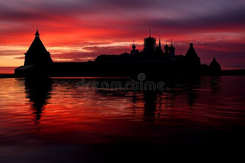 Ilha de Solovki, Rússia Por do sol bonito fantástico acima do lago santamente com a silhueta do monastério de Solovetsky fotografia de stock