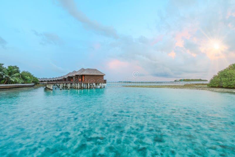 Ilha de surpresa em Maldivas, na casa de campo da água, na ponte de madeira e nas águas bonitas de turquesa com fundo do nascer d foto de stock