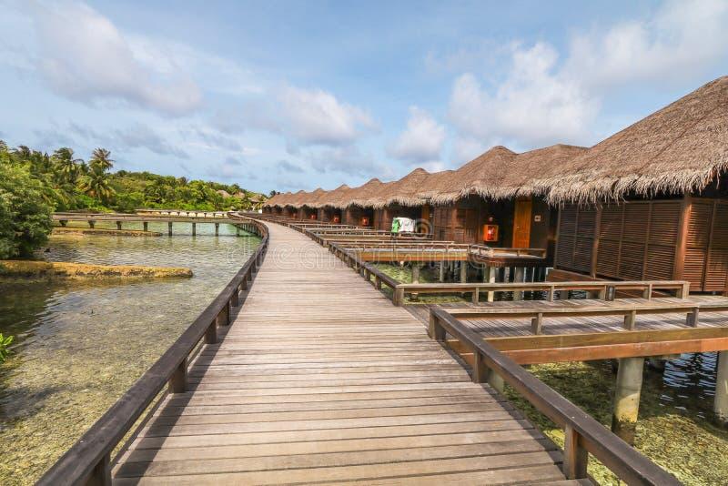 Ilha de surpresa em Maldivas, na casa de campo da ?gua, na ponte de madeira e nas ?guas bonitas de turquesa com fundo do c?u azul foto de stock