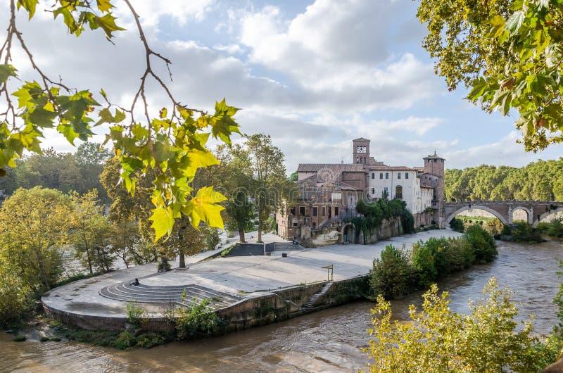 A ilha de Tiberina, cercada pela vegetação e as árvores lavaram pela água do rio de Tibre na capital de Itália, Roma imagem de stock