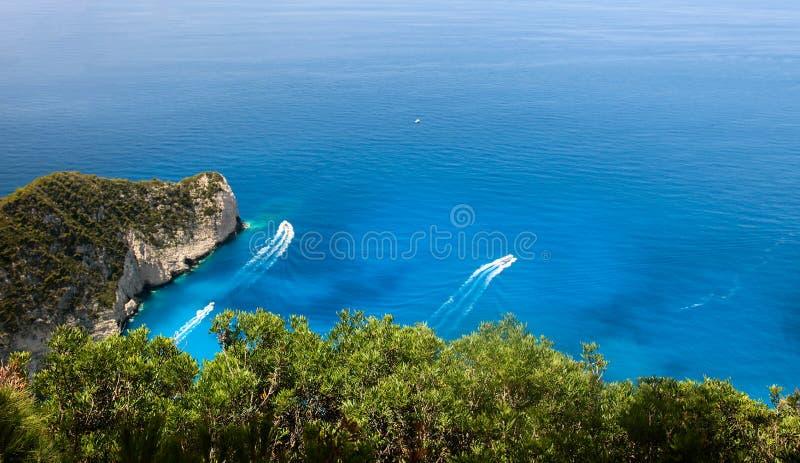 Ilha de Zakynthos, Gr?cia Vista nos barcos, na costa rochosa e na turquesa, águas claros do mar Ionian fotografia de stock