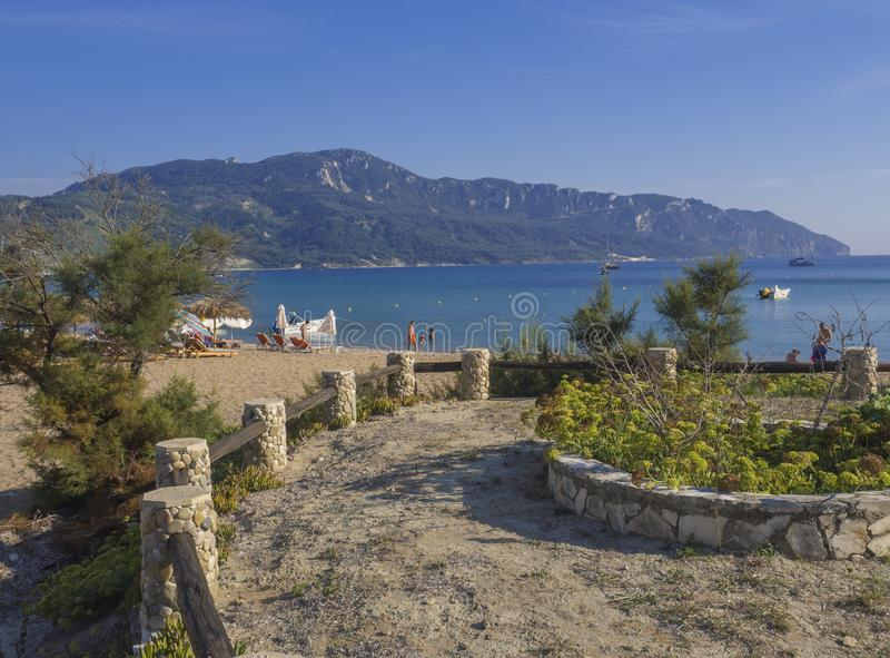 A ilha do onCorfu da praia da areia de Agios Georgios Pagon, Grécia viu do passeio com os potenciômetros de flor, com as camas do fotos de stock royalty free