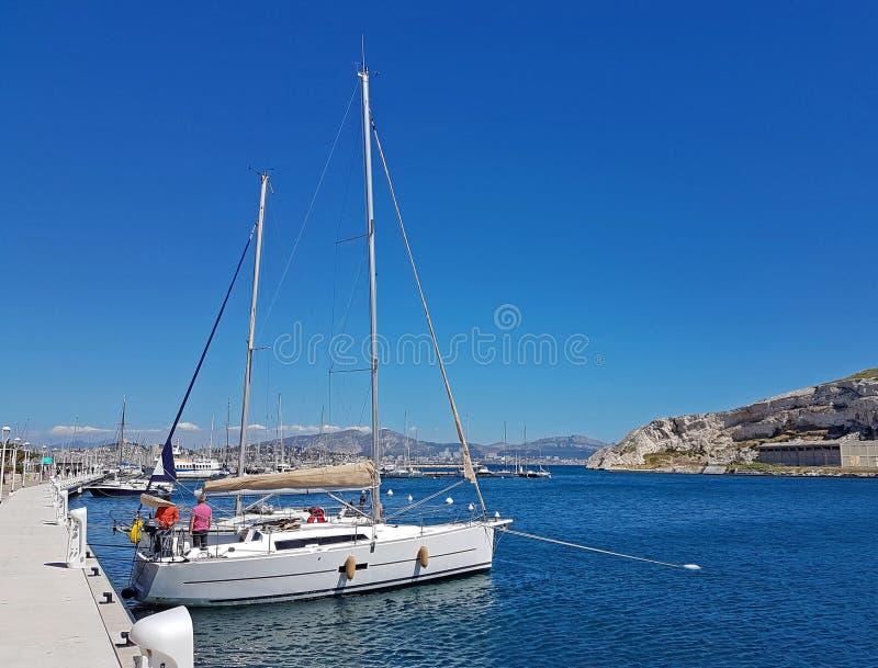 Ilha/França de Ratonneau - podem 8, 2017: O grupo do sailingboat prepara nosso iate à navigação Pouca amarração do iate perto do  fotografia de stock royalty free
