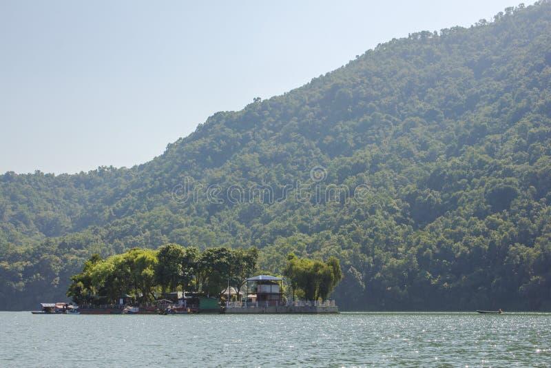 Ilha no lago com casas e árvores no fundo de montanhas verdes e do céu azul imagem de stock royalty free