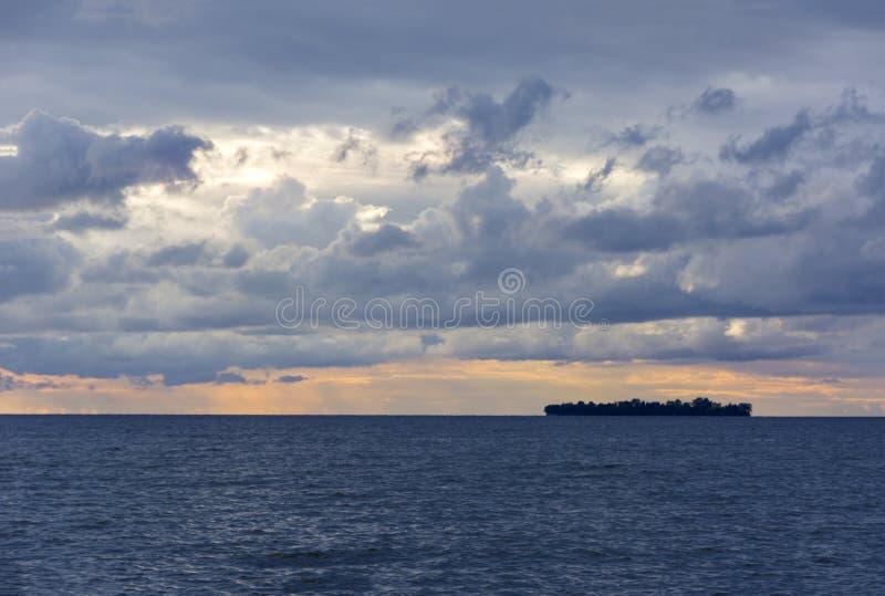Ilha no mar no por do sol, nuvens no céu sobre o mar, baía fotografia de stock