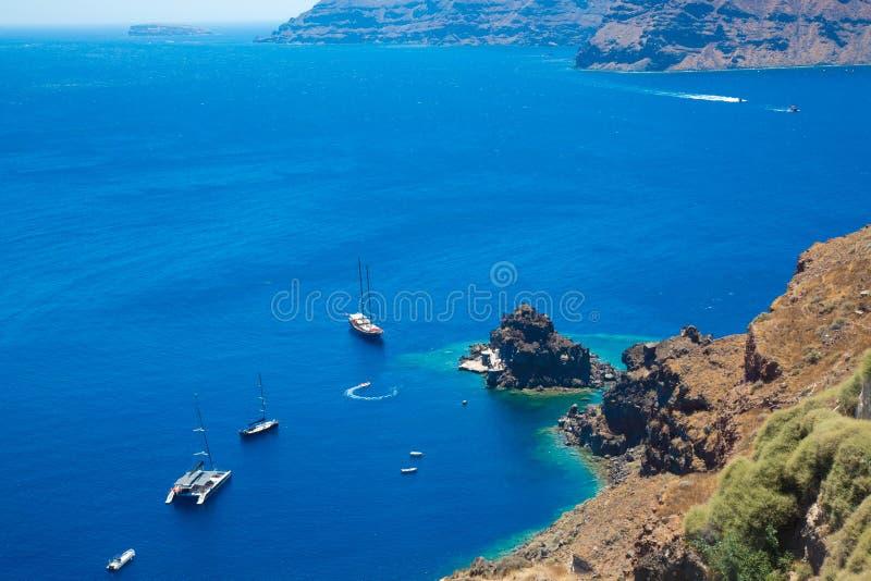 Ilha Santorini, Creta, Gr?cia: Navios brancos dos barcos do cruzeiro no mar azul do fundo Vista superior imagens de stock royalty free