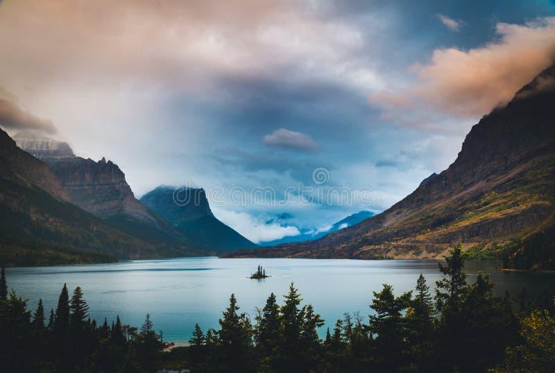 Ilha selvagem do ganso sob nuvens coloridas Parque nacional de geleira, Montana fotos de stock royalty free