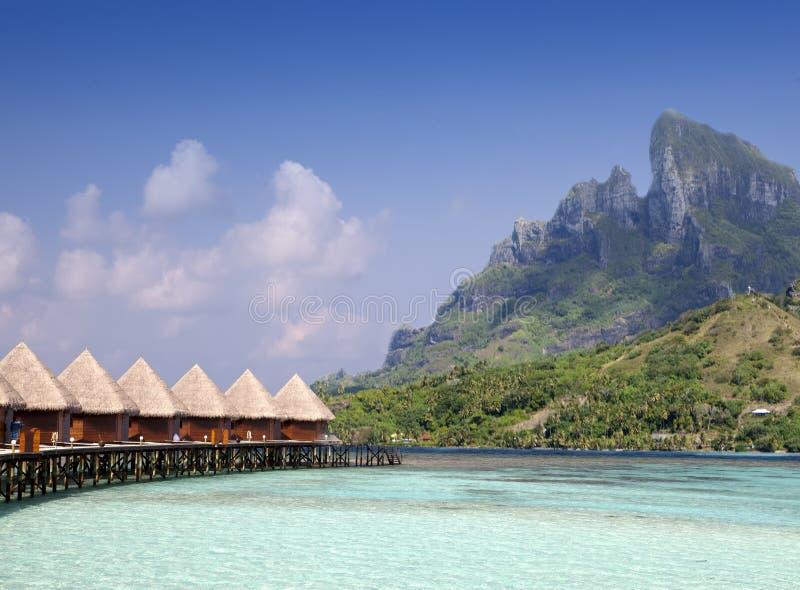 Ilha tropical bonita de Maldivas, casas de campo da água, bungalow no mar e a montanha em um fundo imagem de stock royalty free