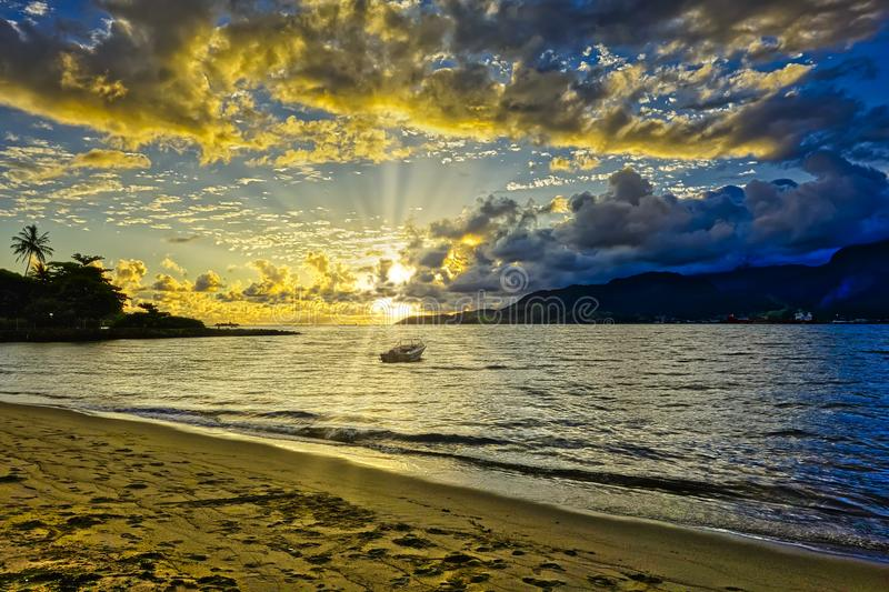 Ilhabela beach Pereque with boat in the sea at sunset - Sao Paulo, Brazil - wide angle photo royalty free stock image