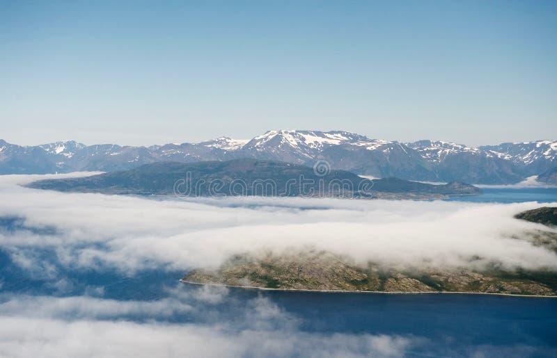 Ilhas cobertas por nuvens em águas frias do fiorde norvegian imagens de stock royalty free