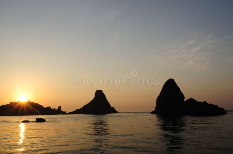Ilhas dos Cyclops em Dawn Sicily Italy - terras comuns criativas pelo gnuckx imagens de stock