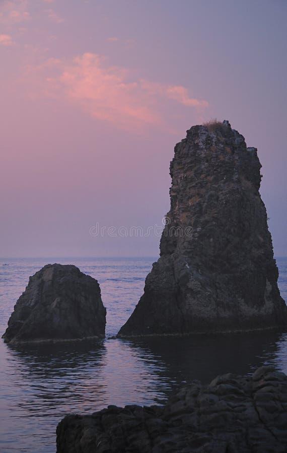 Ilhas dos Cyclops em Dawn Sicily Italy - terras comuns criativas pelo gnuckx imagem de stock