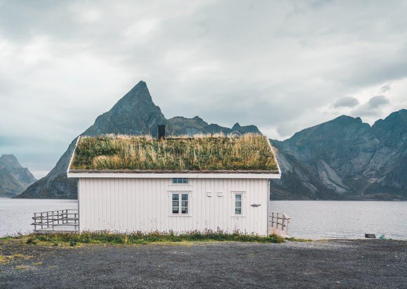 Ilhas Noruega de Lofoten - em setembro de 2018: Casa com o telhado e as montanhas tradicionais da grama no fundo em um nebuloso fotografia de stock