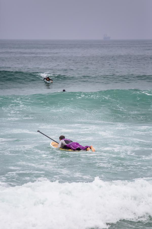 Beach view with professional surfers and Standup Paddleboarding doing extreme maneuvers in sea with waves stock photos