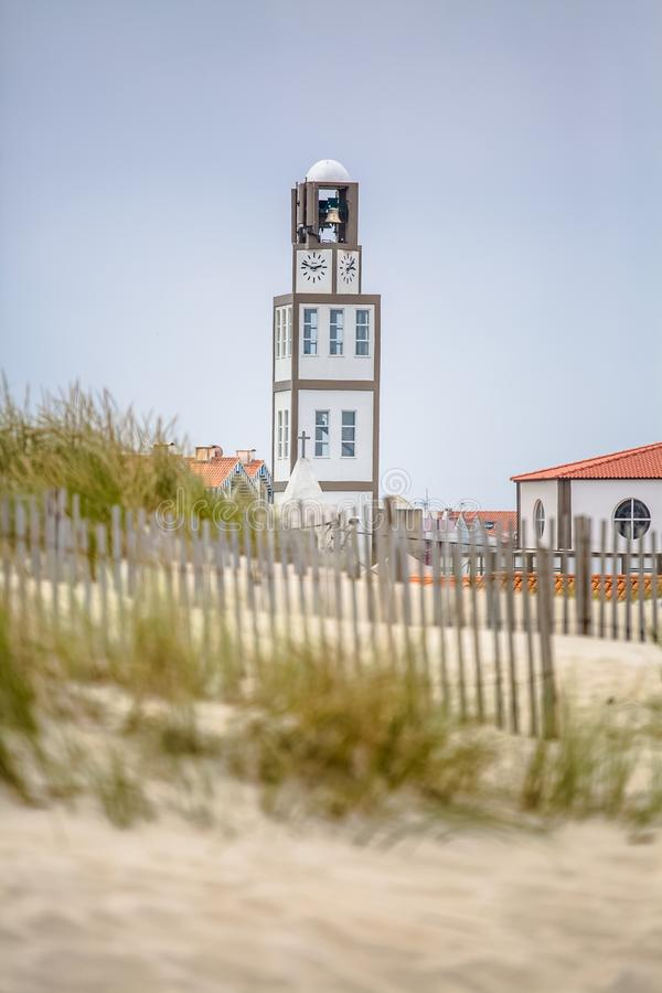 View of a church tower with clock and bell, next to the beach dunes stock photo