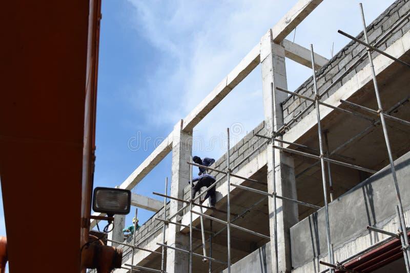 Ilipino byggnadsarbetare som installerar metall, leda i rör ställningar på höghus utan den skyddande dräkten royaltyfri bild