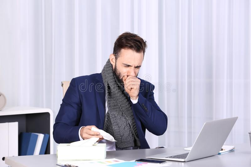 Ill businessman suffering from cough. In office stock image