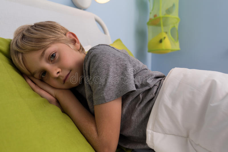 Ill child lying in hospital bed royalty free stock photography