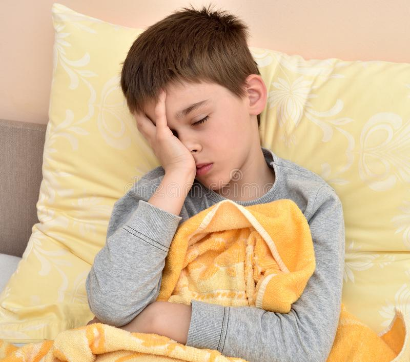 Young boy sitting in bed with headache stock photo