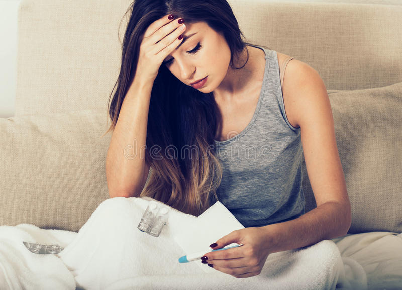 Ill del naso di salto della giovane donna a letto con la temperatura fotografia stock
