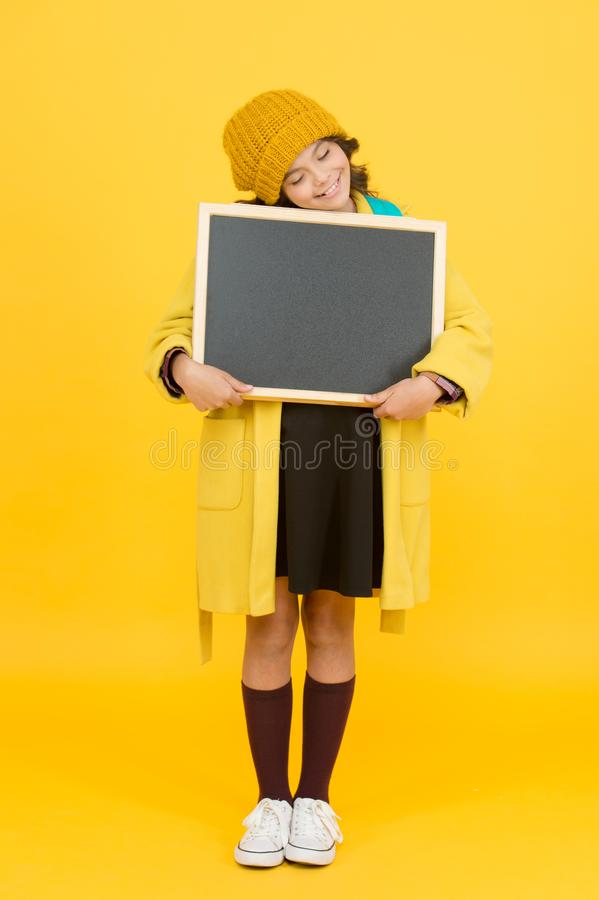 Ill do my own homework. Small child hold empty blackboard for homework on yellow background. School homework assignment stock photography