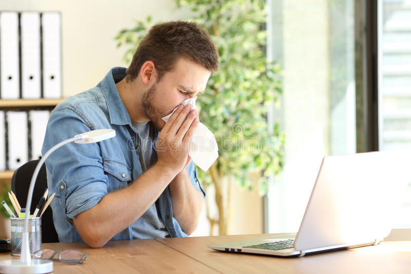 Ill entrepreneur sneezing at office royalty free stock photography