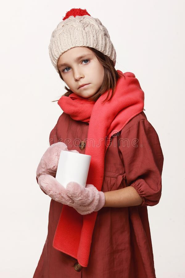 The ill girl holds a cup of tea, medicine, got sick. In a jacket, a cap, gloves, a disease, cold, flu, winter, fall. On a white background in studio royalty free stock photo