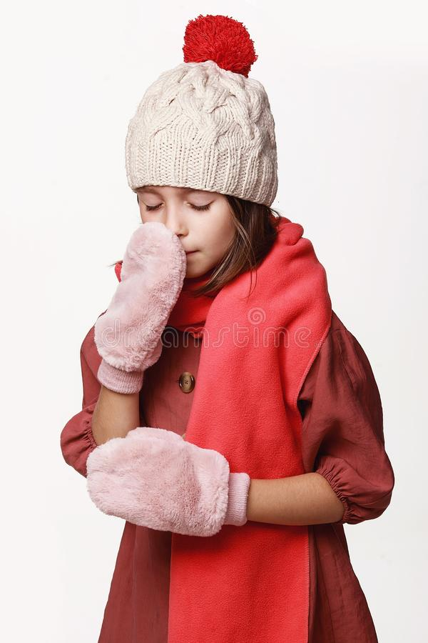 The ill girl in a jacket, a cap, gloves, a disease, cold, flu, winter, fall. Immunity. On a white background in studio royalty free stock photo