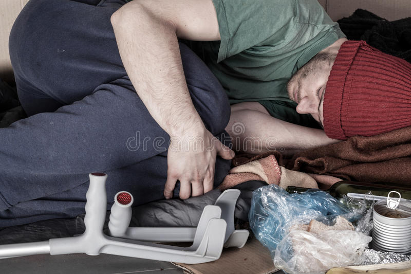 Ill homeless man lying on the street royalty free stock photography