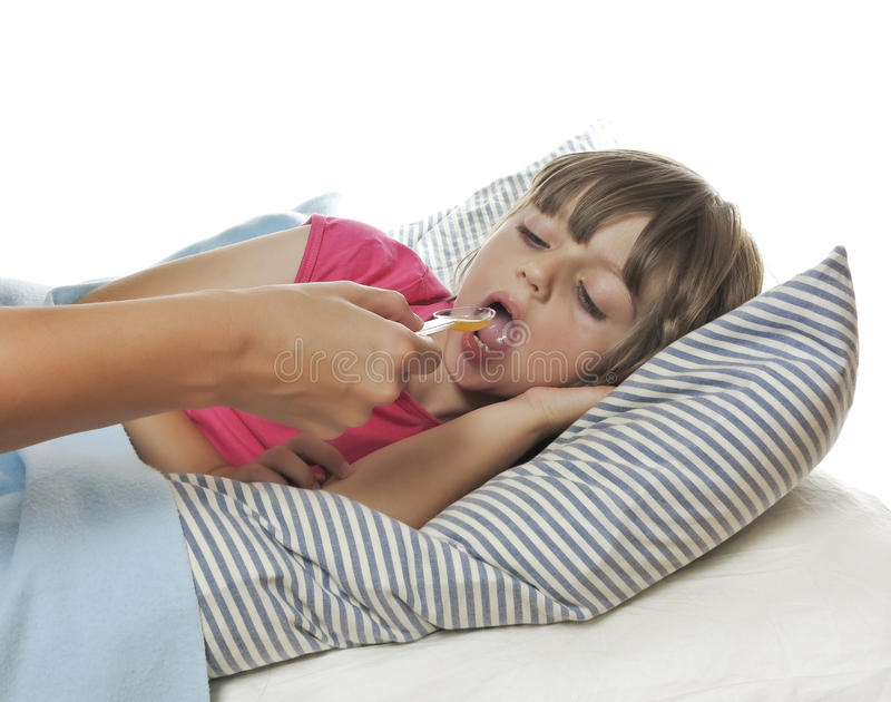 Ill little girl taking cough syrup stock images
