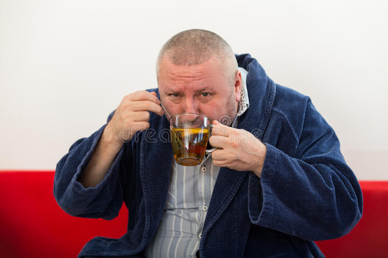 Ill man blowing his nose with paper napkin and drinking tea at home.  stock photography