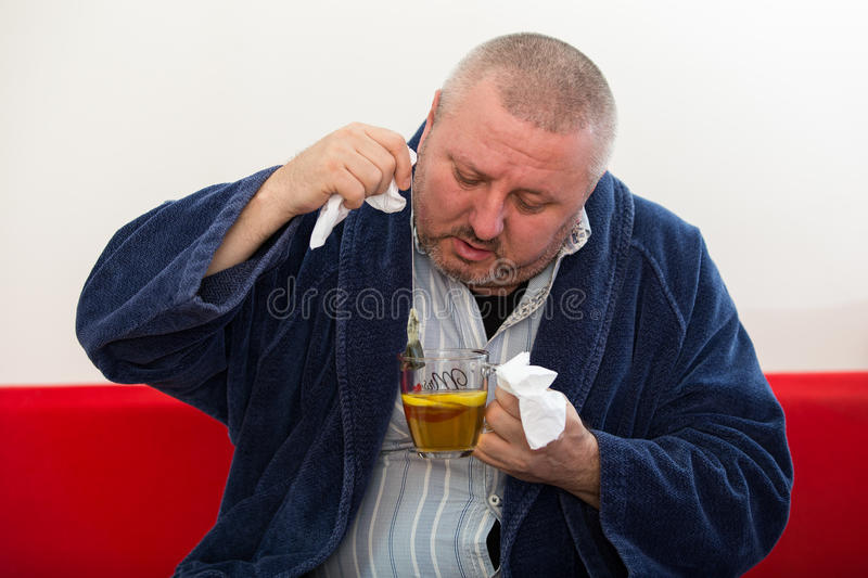 Ill man blowing his nose with paper napkin and drinking tea at home.  stock image