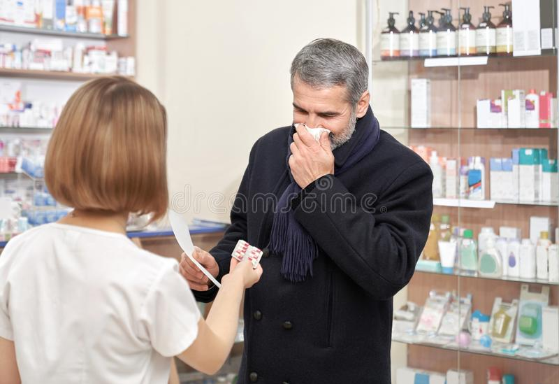 Ill man covering mouth with tissue in drugstore. stock image