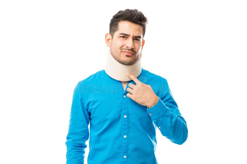 Ill Man Touching Neck Brace While Suffering From Pain stock image