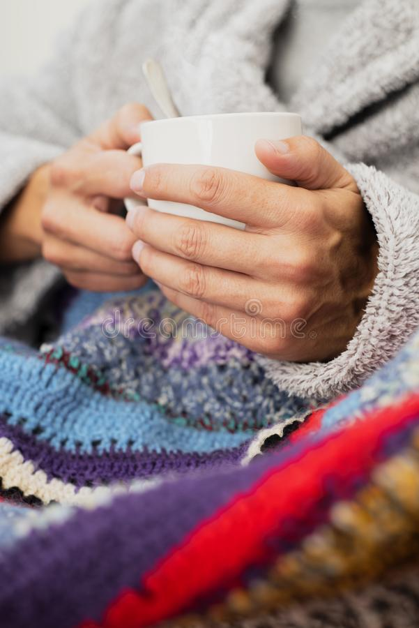 Ill man warming up with a cup of soup. Closeup of an ill young caucasian man at home wearing a fluffy house robe and wrapped in a colorful knitted blanket royalty free stock photos