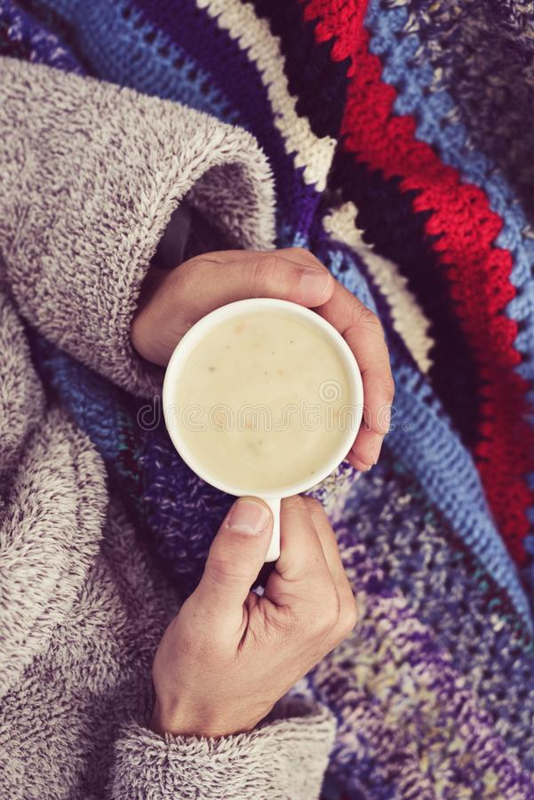 Ill man warming up with a cup of soup. High-angle view of an ill young caucasian man at home wearing a fluffy house robe and wrapped in a colorful knitted royalty free stock photography