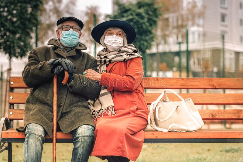 Ill senior couple with face masks relaxing on bench in park stock images