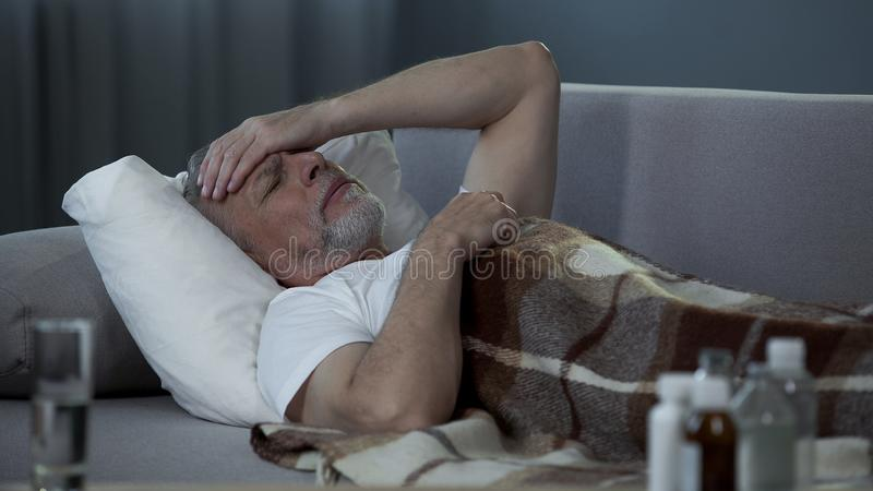 Ill senior male lying in bed and suffering from terrible headache, disease royalty free stock photos