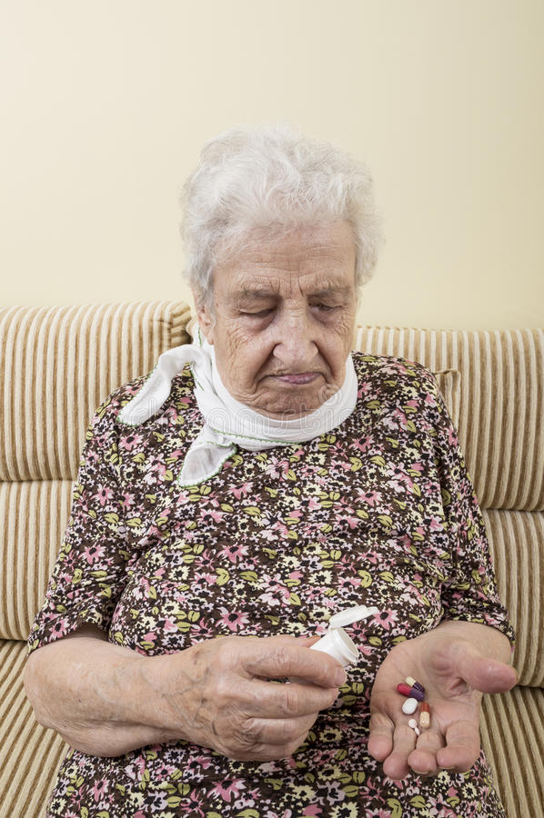 Ill senior woman holding pills on palm stock image