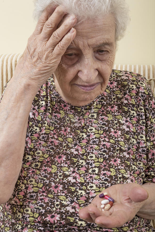 Ill senior woman holding pills on palm royalty free stock image