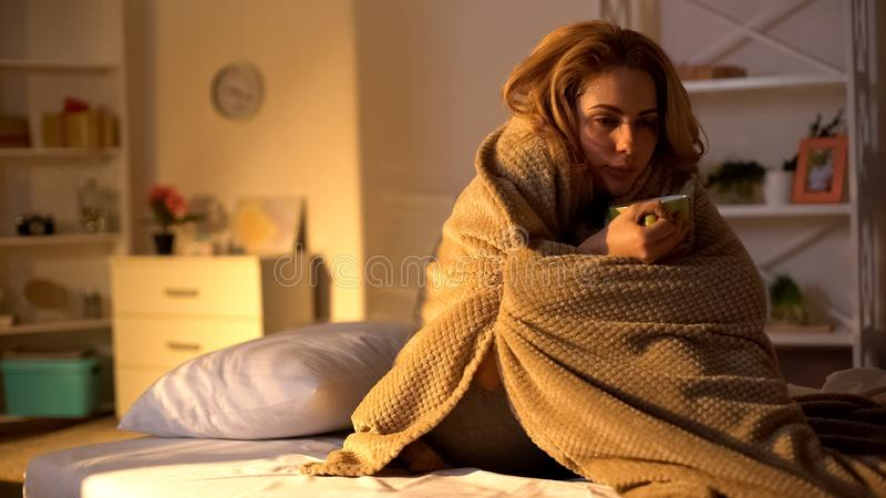 Ill von Decken bedeckte Frauen mit heißem Tee im Bett, das Virus der Gesundheitsversorgung lizenzfreie stockbilder