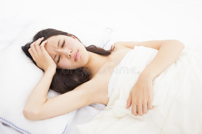 Ill woman in bed. Touching her head royalty free stock photography