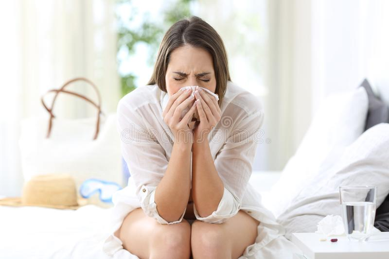 Ill woman coughing in an hotel on vacations stock photos