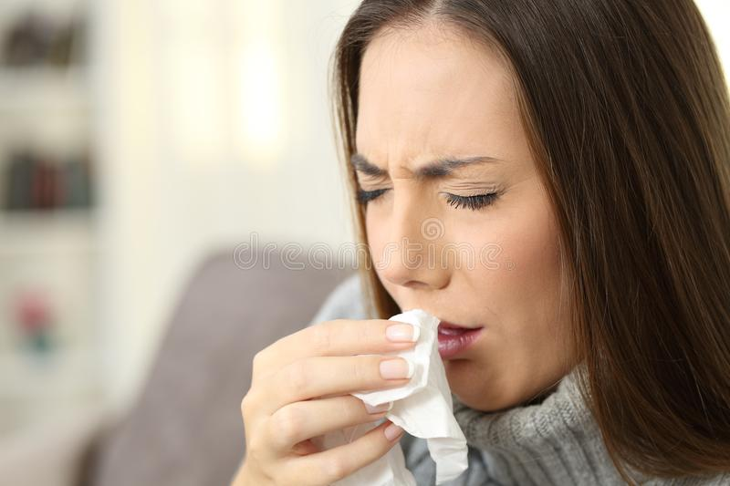 Ill woman coughing using a tissue royalty free stock image