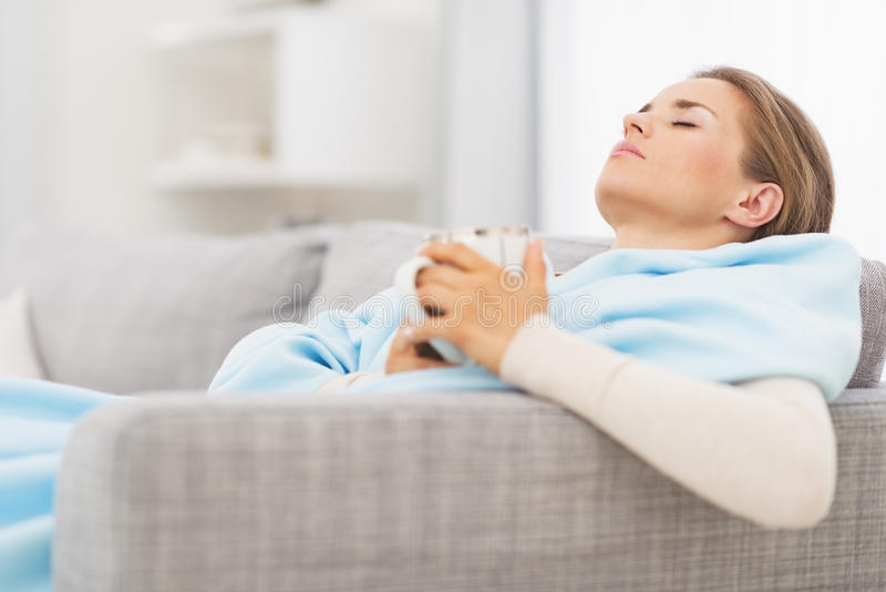 Ill woman with cup of hot beverage sitting on couch