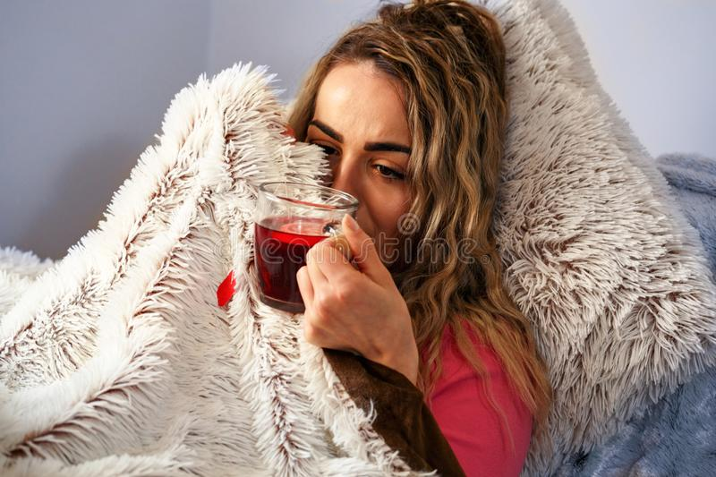 Ill woman, Drinking herbal tea. Vitamins and hot tea for flu. Woman Caught Cold. Virus royalty free stock image