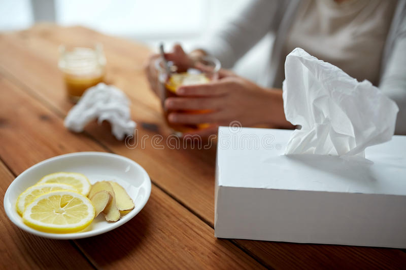 Ill woman drinking tea with lemon and ginger royalty free stock image