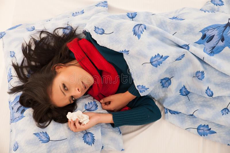 Ill woman with flu blows in handkerchief isolated over white background stock photography