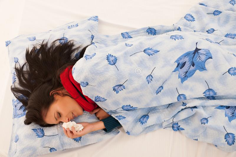 Ill woman with flu blows in handkerchief isolated over white background royalty free stock image